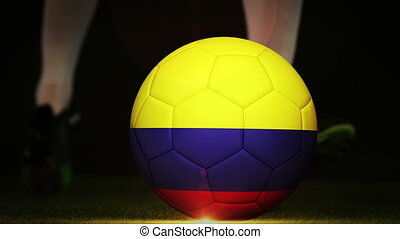 Football player kicking colombia flag ball on black...