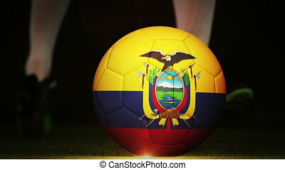 Football player kicking ecuador flag ball on black...