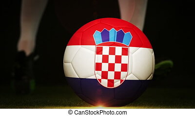 Football player kicking croatia flag ball on black...
