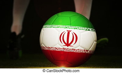 Football player kicking iran flag ball on black background...