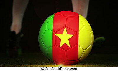 Football player kicking cameroon flag ball on black...