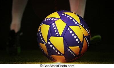Football player kicking bosnia flag ball on black background...
