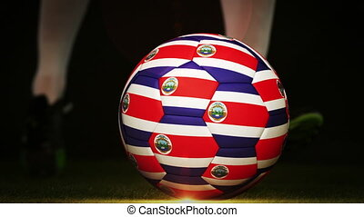 Football player kicking costa rica flag ball on black...