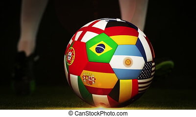 Football player kicking international flag ball on black...