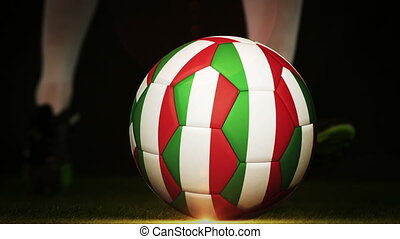 Football player kicking italy flag ball on black background...