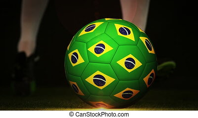 Football player kicking brazil flag ball on black background...