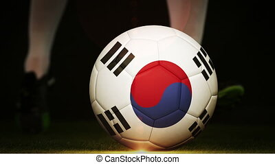 Football player kicking korea republic flag ball on black...
