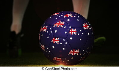 Football player kicking australia flag ball on black...