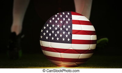Football player kicking usa flag ball on black background in...