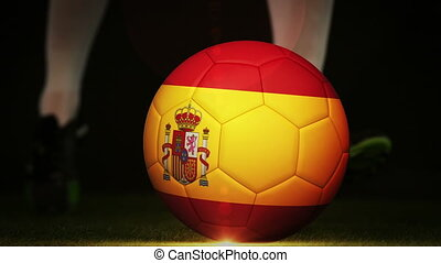 Football player kicking spain flag ball on black background...