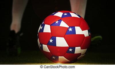 Football player kicking chile flag ball on black background...