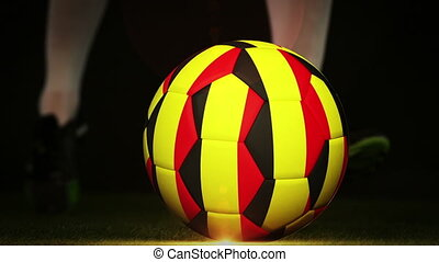 Football player kicking belgium flag ball on black...