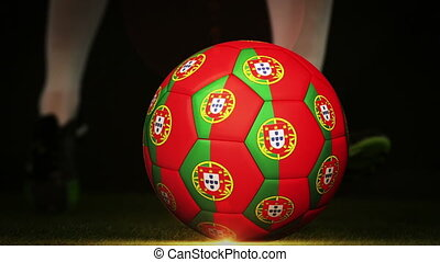 Football player kicking portugal flag ball on black...