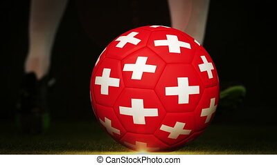 Football player kicking swiss flag ball on black background...