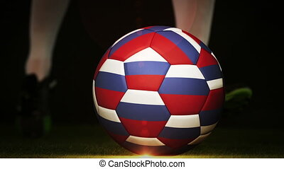 Football player kicking russia flag ball on black background...