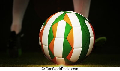 Football player kicking ivory coast flag ball on black...