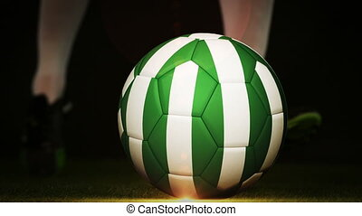 Football player kicking nigeria flag ball on black...