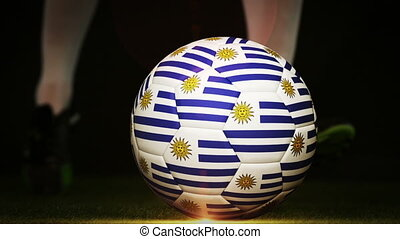 Football player kicking uruguay flag ball on black...