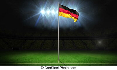 Germany national flag waving on flagpole on football pitch...