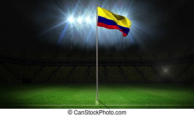Colombia national flag waving on flagpole on football pitch...
