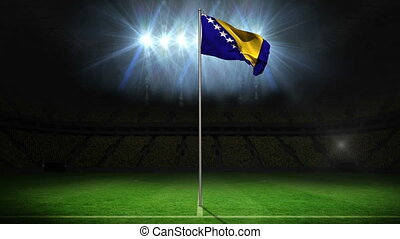 Bosnia national flag waving on flagpole on football pitch...
