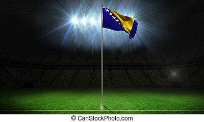 Bosnia national flag waving on flagpole on football pitch...