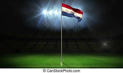 Netherlands national flag waving on flagpole on football...