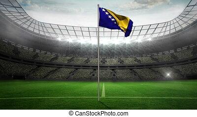 Bosnia national flag waving on flagpole in football stadium...