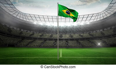 Brazil national flag waving on flagpole in football stadium...