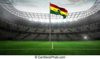 Ghana national flag waving on flagpole in football stadium...