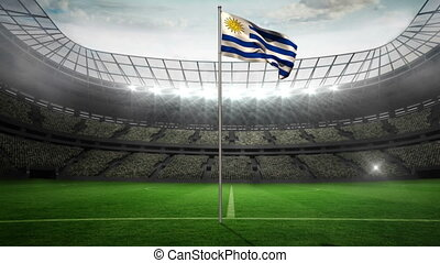 Uruguay national flag waving on flagpole in football stadium...