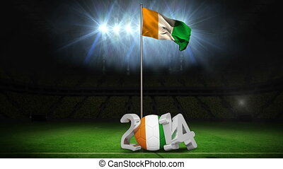 Ivory Coast national flag waving on football pitch on black...
