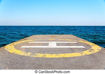 Helipad on a concrete pier near the sea against a clear sky....