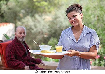 home carer serving meal to elderly man - smiling home carer...
