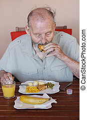 elderly man eating healthy lunch in care home