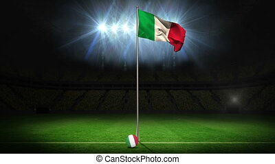 Italy national flag waving on flagpole on football pitch...