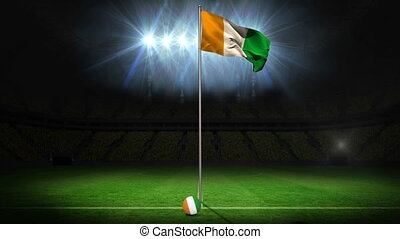 Ivory Coast national flag waving on flagpole on football...