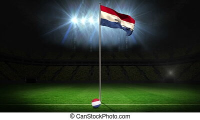 Netherlands national flag waving on flagpole on football...