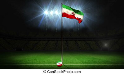 Iran national flag waving on flagpole on football pitch with...