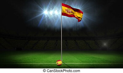 Spain national flag waving on flagpole on football pitch...