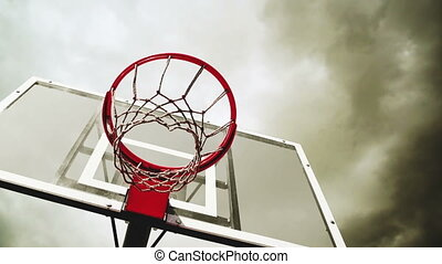 Basketball hoop with clouds time lapse footage in background...