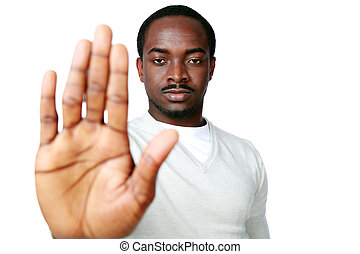 Young african man showing stop sign with hand over white...