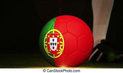 Football player kicking Portugal flag ball - Football player...