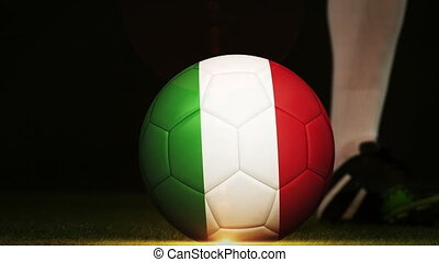 Football player kicking italy flag ball on black background