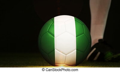 Football player kicking Nigeria flag ball - Football player...