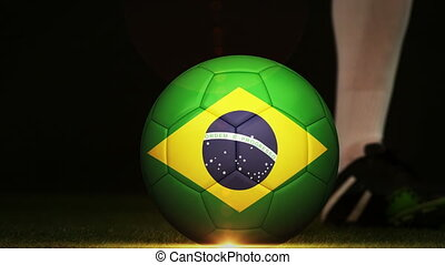Football player kicking Brazil flag ball - Football player...