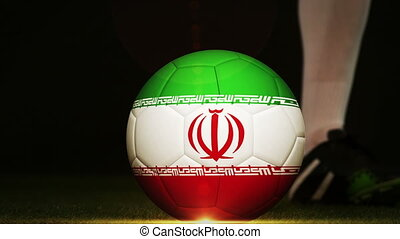 Football player kicking Iran flag ball - Football player...