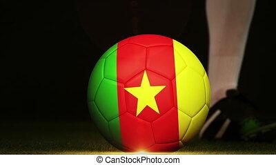 Football player kicking cameroon flag ball on black...