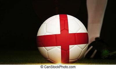 Football player kicking England flag ball - Football player...