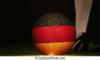 Football player kicking Germany flag ball - Football player...